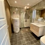 Big bathroom with toilet, shower, sink and mirror.