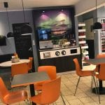 Coffee corner at the gas station, Best, with orange chair and tables and a coffee machine.