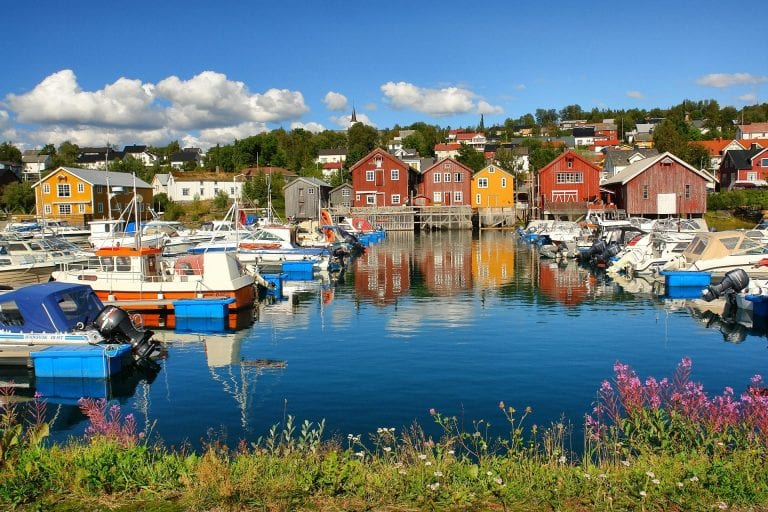 Beautiful and colorful photo of boat houses next to the marina at Hemnesberget with boats and flowers in the foreground.
