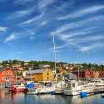 Beautiful and colorful photo of boat houses next to the marina at Hemnesberget with boats in the front on a clear summer day.