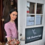 "Beautiful Sandra holding a nice cake in her hands while standing invitingly behind the door to her own ""Lille Havfruen kafe"""