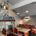 Cozy restaurant room with wooden walls and red wooden furniture.