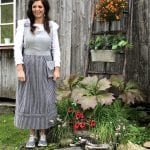Ann Synnøve, dressed in an old costume, standing welcoming in front of her café-entrance at Inderdalen Farm.