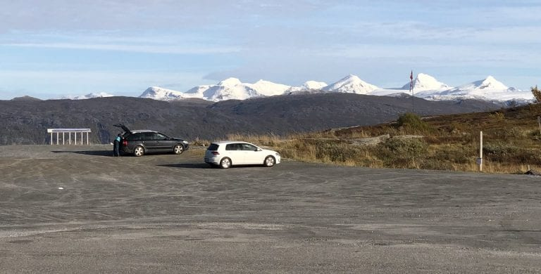 Two cars parked in the parking space at Korgfjellet with a great view of the Okstindan mountains in the horizon.