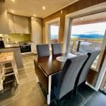 Kitchen with dining table in front om panorama windows and mountain view