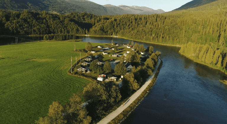 Korgen Camping, seen from above, located right next to Røssåga river and in one corner of a great acre.