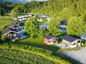 Korgen Camping, seen from above, with its cabins surrounded by beautiful green nature and Røssåga river.