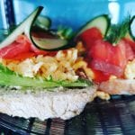 Delicious-looking and colorful salmon sandwich with eggs decorated with cucumber and lettuce at Lille Havfruen Kafé.