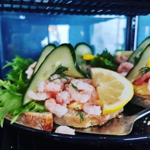 Delicious-looking shrimp sandwich decorated with cucumber, lettuce and lemons at Lille Havfruen Kafé.