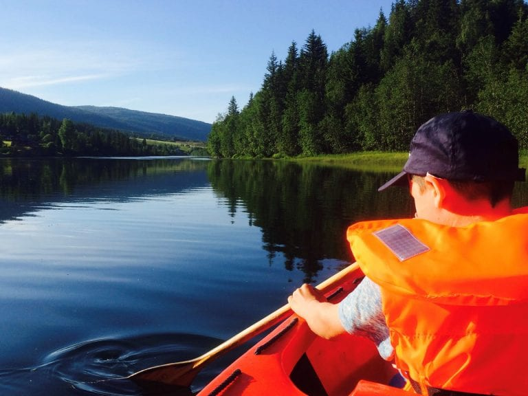 Young boy in a bright orange life jacket paddling in a canoe on Røssåga river, on a quiet and sunny day.