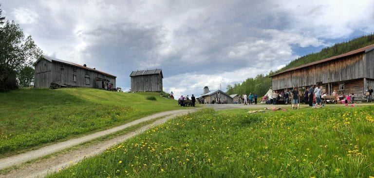 Panorama picture of Inderdalen Farm with people playing and enjoying the beautiful nature surroundings.
