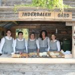 Welcoming staff at Inderdalen Farm dressed in old costumes to match the farm's style, selling local and home-made food.