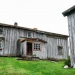 The main building at Inderdalen Farm, a beautiful, old, grey and well-kept wooden building.