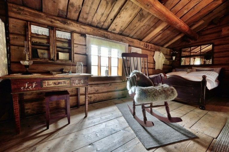 Cozy and old-style bedroom at Inderdalen Farm with a rocking chair, old desk, and bed.