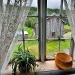 Nostalgic view from a bedroom at Inderdalen Farm, with old curtains in the window and view of the other farm buildings.