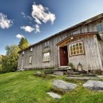 The main building at Inderdalen Farm, a beautiful, old, grey and wooden building with a path of stones leading up to it.