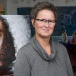 Artist, Yvonne, smiling with her glasses on and standing in front some of her beautiful paintings.