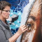 Artist, Yvonne, concentrated while painting the eye of a girl on one of her paintings. Another painting is seen in the back.
