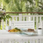 Colorful brunch outside on a white table decorated with flowers, on a white porch in green surroundings.