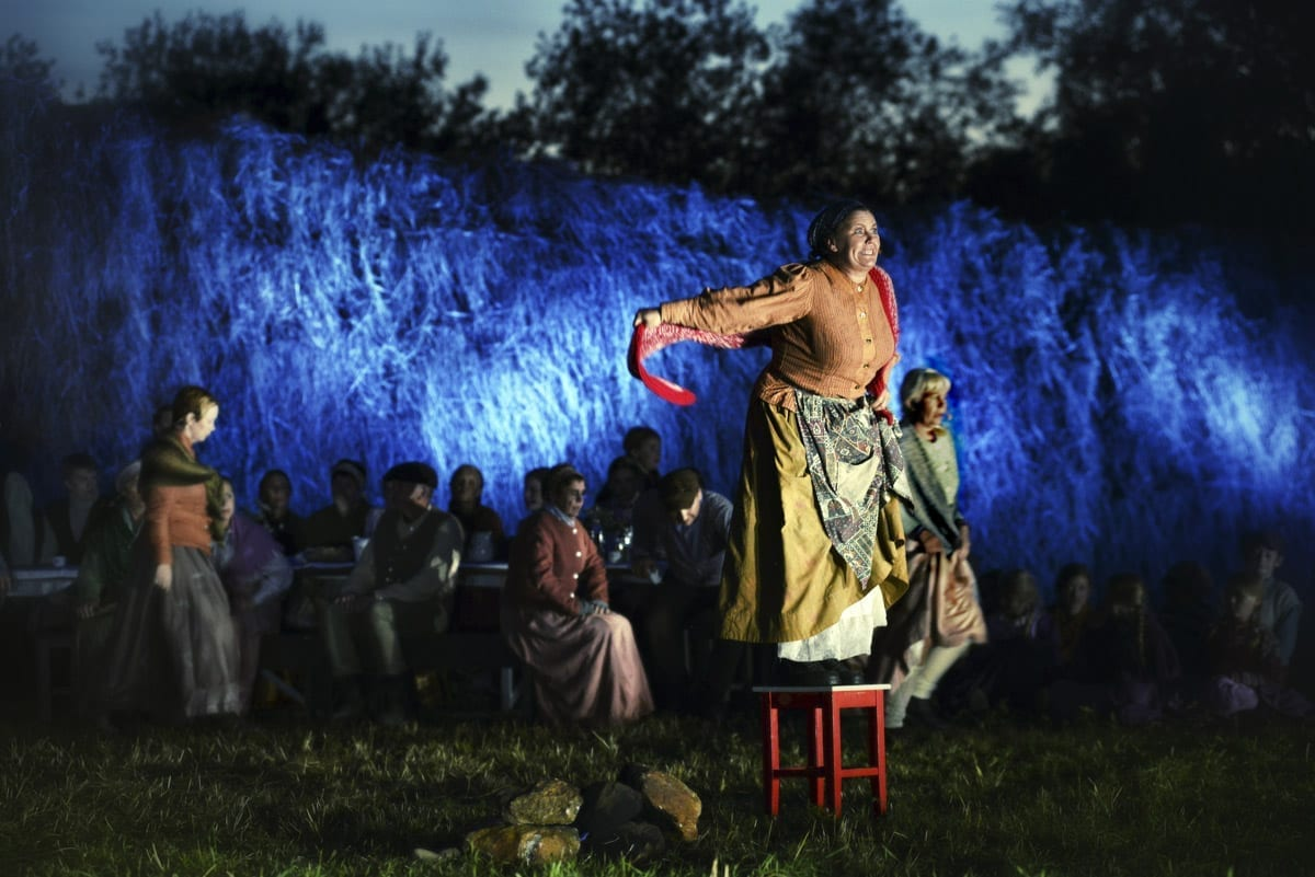 Woman dressed in an old costume standing on a chair and speaking eagerly, during the local play, Klemetspelet.
