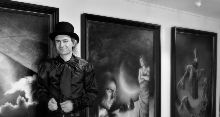 Black-and white photo of the smiling artist, Sigmund, in front of some of his paintings at an exhibition.