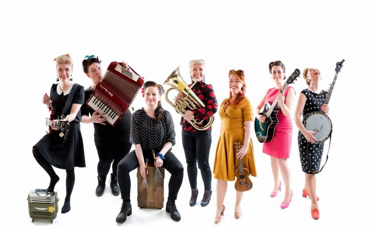 Band-picture of the seven happy and laughing women in Bitchy Big Boobies Bang Band holding their instrument.