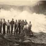 Historic picture of a group of men standing in front of the big and foaming waterfall, Sjøforsen.
