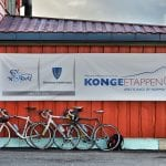 Bikes leaning up against the wall of the red Korgfjellet Fjellstue, underneath an Artic race poster.