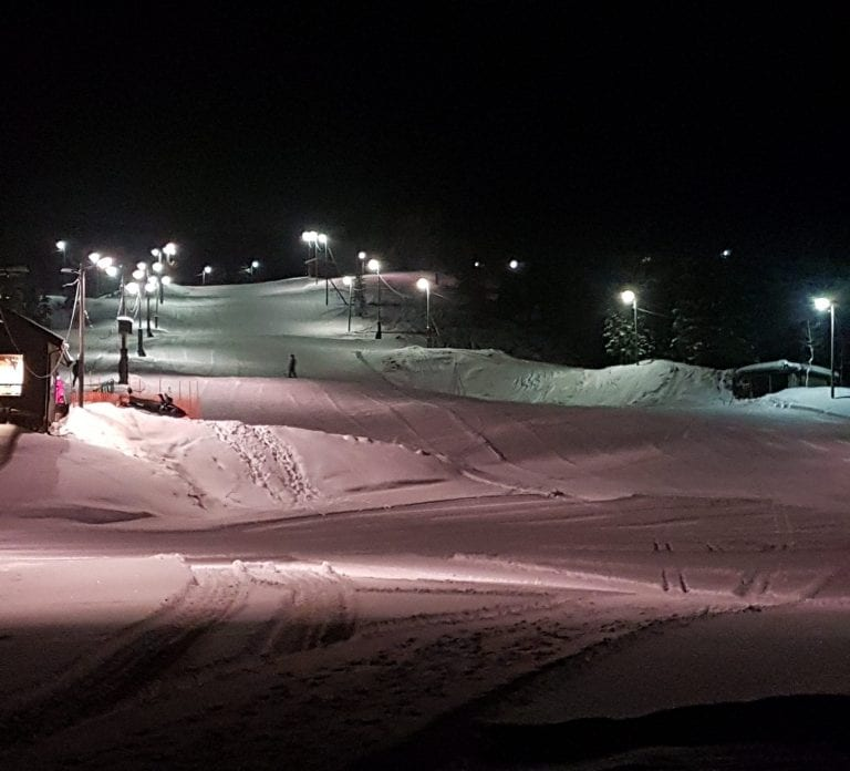 Down hill slopes in Bleikvasslia at night with only the slopes lit up in white and pink lighting.