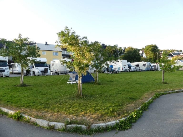Parking for mobile caravan at the marina in the center of Hemnesberget, next to a lawn where one can put up a tent.