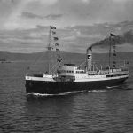 An old black and white photo of the ship DS Nordnorge on the coast.