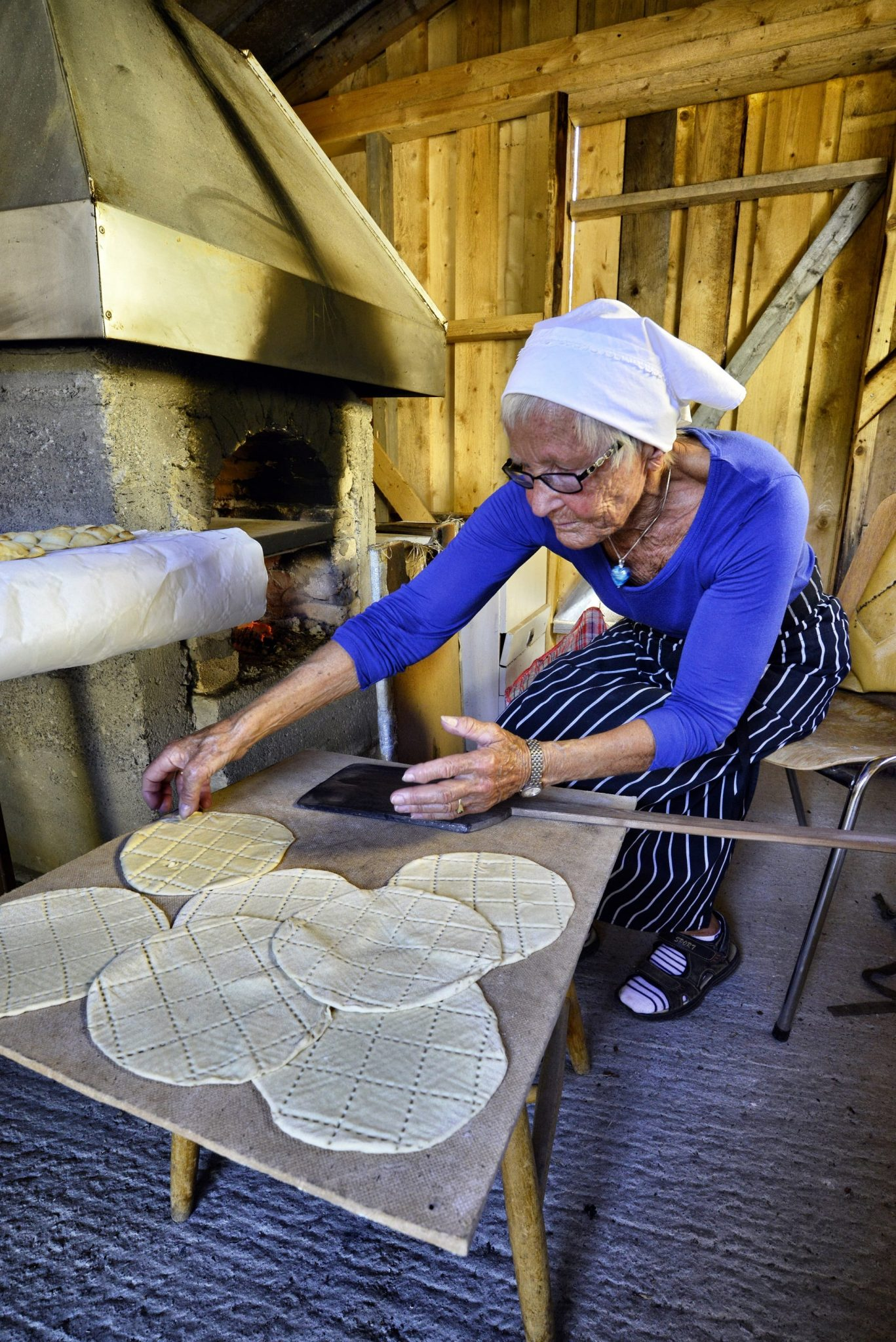 "Elderly lady in blue sitting in front of baking oven with ""kamkaker"" (local pastry) ready to be baked."