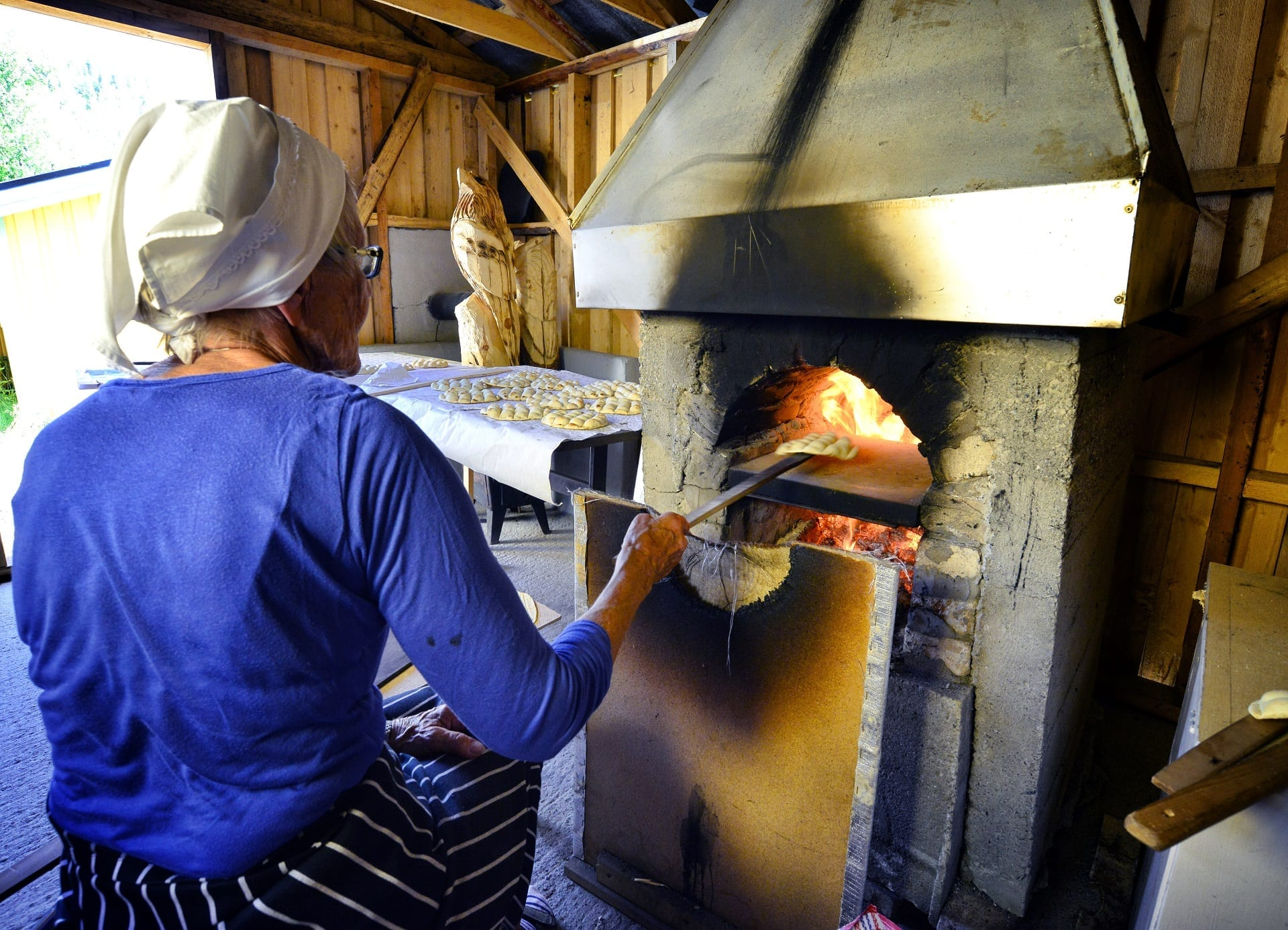 """Elderly lady in blue sitting in front of baking oven with """"kamkaker"""", local bread, ready to be baked."""