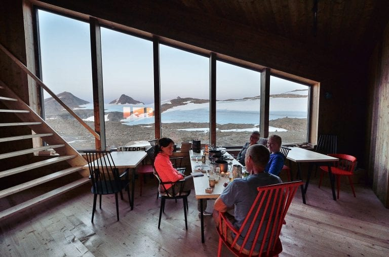 People eating in the dining room at Rabothytta, with big panorama windows showing the view over the glacier