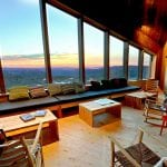 Living room at Rabothytta with a view over a beautiful and colorful sunset seen through the big panorama windows.