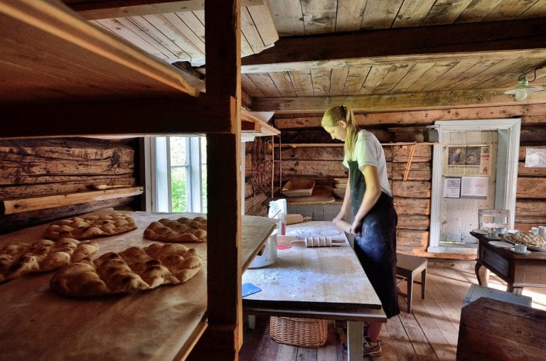 "Young woman baking the local bread, ""kamkake"", inside an old and wooden baking house."