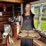 """Smiling young lady holding a tray of freshy made """"kamkake"""", local bread, standing inside the old and wooden baking house."""