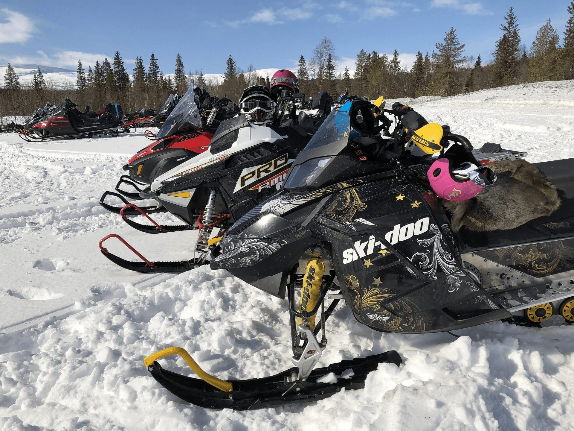 Picture of several colorful snowmobiles standing still in the snow on a sunny day.