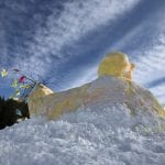 Home-made Easter chicken made from snow with added yellow coloring and a tail of colorful branches as its tail.
