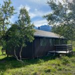 A brown cabin surrounded by birch trees and mount Oksskolten in the background