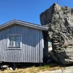 "A small, grey cabin in the mountains during the summer with a huge rock ""leaning"" on the cabin."