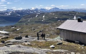 Hikers walking towards the cabin, Gråfjellhytta, during summer with a view over a big lake and more mountains in the horizon.