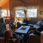 People sitting in a cozy living-room inside a cabin in the mountains with the sun shining in through the windows.