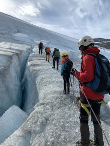 People walking with rope and crampons next to a huge crack in the glacier.