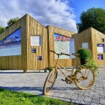 Information board in Korgen made of shining woodwork in the shape of mountains and a matching golden bike in front.