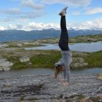 Girl doing a handstand on a rocky peak in front of small lakes with the Okstindan-mountains in the background.