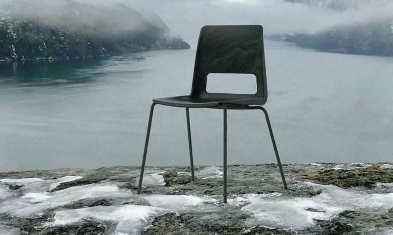 Black chair standing on a mountain rock in foggy surroundings, in front of the fjord and mountains around it.