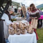 Spectators visiting Jamtjordmartnan and buying local products from one of the venders, dressed in old costumes.