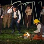 Klemet, sitting next to the fire while a band of men approach him with their scythes, during the local play, Klemetspelet.