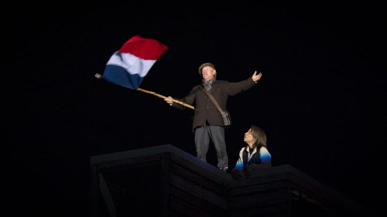 A man dressed in old local costumes, holding the flag of France in complete darkness, during the local play, Klemetspelet.